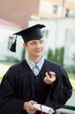 Der Absolvent mit einem Diplom in der Hand und schwarzem Umhang Stockfoto