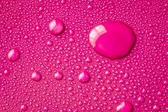 Der abstrakte Wassertropfen auf Oberfläche des neuen vibrierenden rosa backgr Lizenzfreie Stockbilder