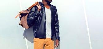 Der afrikanische Mann der Mode, der eine schwarze Radfahrerlederjacke trägt, hält eine Tasche Lizenzfreies Stockbild
