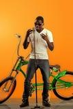 Der afrikanische schwarze Mann, der am Mikrofon mit einem Fahrrad unterstützen singt herein, auf orange Hintergrund Stockfoto