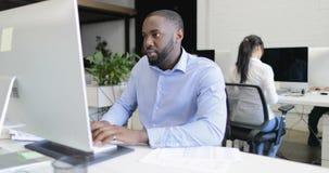 Der AfroamerikanerGeschäftsmannmanager, der an Computer mit Wirtschaftlern arbeitet, team im modernen kreativen Büro