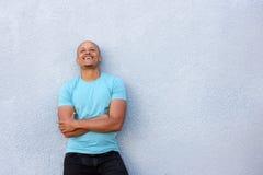 Der Afroamerikanerkerl, der mit den Armen lacht, kreuzte oben schauen Stockfotografie