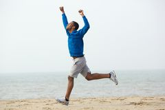 Der Afroamerikanermann, der mit den Händen läuft, hob am Strand an Stockfotos