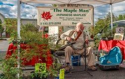 Der Ahorn-Mann, der Gitarre, den Gesang und den Verkauf spielt Stockfotografie