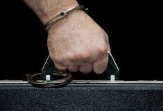 Der Aktenkoffer mit Handschellen gefesselt zu seiner Hand Lizenzfreie Stockbilder