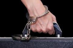 Der Aktenkoffer mit Handschellen gefesselt zur weiblichen Hand Lizenzfreie Stockfotos