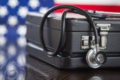 Der Aktenkoffer und Stethoskop, die auf Tabelle mit amerikanischer Flagge stillstehen, sind Stockfotos