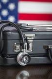 Der Aktenkoffer und Stethoskop, die auf Tabelle mit amerikanischer Flagge stillstehen, sind Stockbild