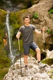 Der aktive junge Mann, der in den Bergen wandert, nähern sich Wasserfall auf einem Nebenfluss Stockbild