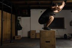 Der aktive Mann, der Kasten tut, springt in eine Turnhalle Stockfoto