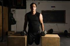 Der aktive Mann, der tricep tut, taucht in eine Turnhalle ein Lizenzfreie Stockfotos