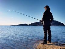 Der aktive Mann fischt auf Meer von der felsigen Küste Fischerkontrolle, die Köder drückt Stockfotografie