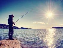 Der aktive Mann fischt auf Meer von der felsigen Küste Fischerkontrolle, die Köder drückt Stockbild