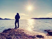 Der aktive Mann fischt auf Meer von der felsigen Küste Fischerkontrolle, die Köder drückt Stockfoto