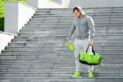 Der aktive muskulöse Mann, der Schüttel-Apparat halten und der Sport bauscht sich, draußen Lizenzfreie Stockbilder