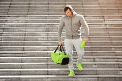 Der aktive muskulöse Sportmann, der Schüttel-Apparat halten und der Sport bauscht sich und draußen bildet aus Lizenzfreie Stockfotos