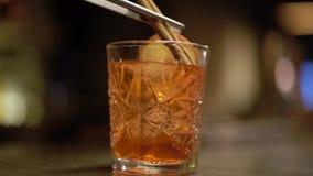 Der Alkohol, der mit Orange und Eis geschossen wird, ist am Tabellenabschluß oben Barmixer setzt Zimt in das Glas ein stock video footage