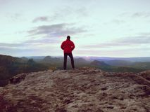 Der alleintourist mit Kappe und die sportliche Kleidung im Freien steht auf Klippenrand aufpassend in Nationalparktal Lizenzfreie Stockbilder