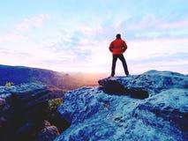 Der alleintourist mit Kappe und die sportliche Kleidung im Freien steht auf Klippenrand aufpassend in Nationalparktal Lizenzfreies Stockfoto