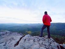 Der alleintourist mit Kappe und die sportliche Kleidung im Freien steht auf Klippenrand aufpassend in Nationalparktal Stockfotos