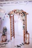 Der Altar an der Hochzeitszeremonie wird mit Floristen verziert Blumen und ein hölzerner Bogen mit großen Kerzenständern Lizenzfreie Stockfotos