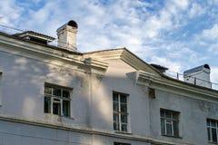 Der Altbau, ein Haus mit Kaminen gegen den blauen Himmel bei Sonnenuntergang Heraus getragen ummauern Sie mit Flecken des Rosts Stockbilder