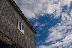 Der Altbau mit Fenster gegen einen blauen Himmel mit Wolken Lizenzfreies Stockfoto