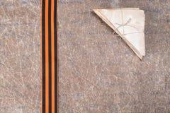 Der alte Buchstabe und das St- George` s Band liegen auf zerknittertem Papier Lizenzfreie Stockfotos