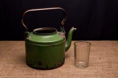 Der alte Eisenkessel und das facettierte Glas auf dem Tisch Stockbilder