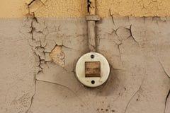 Der alte elektrische Schalter und das Kabel auf einer altersschwachen Wand Lizenzfreies Stockfoto