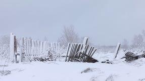 Der alte faule Zaun auf einem weißen schneebedeckten Gebiet des Winters Lizenzfreie Stockbilder