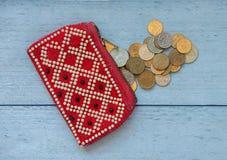 Der alte Geldbeutel auf dem Tisch und Münzen Stockbild