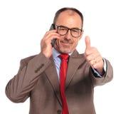 Der alte Geschäftsmann, der am Telefon spricht, macht das okayzeichen Lizenzfreies Stockfoto