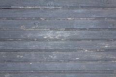 Der alte hölzerne graue Zaun, der von den Planken mit der Schale der Farbe hergestellt werden, die Sprünge und die weißen Stellen lizenzfreie stockfotos