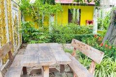 Der alte Holztisch und der Stuhl im Garten Lizenzfreie Stockfotos