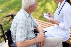 Der alte Mann auf einem Rollstuhl verständigend mit dem Doktor im Sommerpark Doktor hält ein Notizbuch in seiner Hand Lizenzfreie Stockfotografie