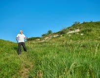 Der alte Mann, der auf grünes Feld mit der Spurhaltung geht, haftet Stockbild