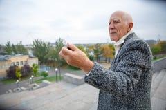 Der alte Mann betrachtet die Aktionskamera, die er in seiner Hand hält Draußen auf der Straße Stockfotografie