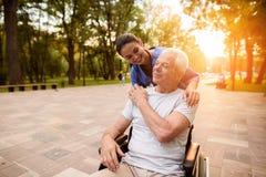 Der alte Mann, der in den Griffen eines Rollstuhls die Krankenschwester durch die Hand sitzt, die ihre Hand auf seine Schulter le Stockfotos