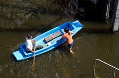 Der alte Mann, der ein Boot rudert, um Flutopfern zu helfen stockfoto