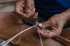 Der alte Mann, der ein Seil für bindet, machen einen Drachen Stockfotos