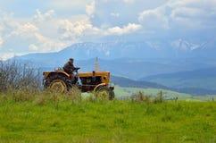 Der alte Mann, der an einem Traktor arbeitet Lizenzfreie Stockfotografie