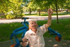 Der alte Mann, der herein Sport auf einem Straßensimulator anstrebt Lizenzfreie Stockfotos