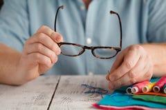 Der alte Mann, der an schaut, nähen Nadelwurfsgläser Stockfotografie