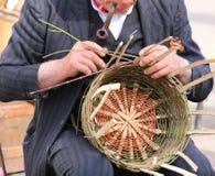 der alte Mann, der sein Rohr raucht, stellt einen Strohkorb her Lizenzfreie Stockbilder
