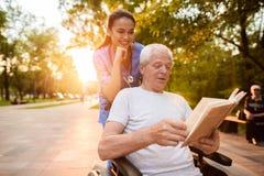 Der alte Mann, der in einem Rollstuhl sitzt, liest ein Buch Eine Krankenschwester hinter dem alten Mann und das Buch auch betrach Lizenzfreie Stockfotos
