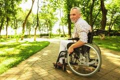 Der alte Mann in einem Rollstuhl sitzt mitten in der Gasse im Park Er lächelt Lizenzfreies Stockfoto