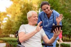Der alte Mann, der in einem Rollstuhl und in der Krankenschwester sitzt, passen etwas auf, das auf der alter Mann ` s Tablette in Lizenzfreie Stockfotografie