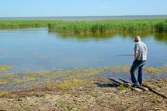 Der alte Mann fängt Fische eine Stange in einem Nebenfluss der Ostsee Stockfotografie