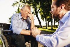Der alte Mann ist auf einem Rollstuhl und dem Mann im Park Der alte Mann ist, der Mann versucht, ihn zu stützen traurig Stockfotografie